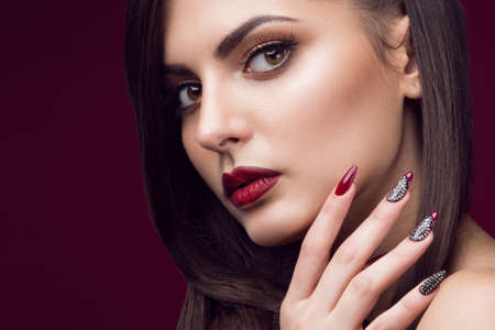 Pretty girl with unusual hairstyle, bright makeup, red lips and manicure design. Beauty face. Art nails. Studio portrait Stockfoto