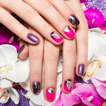 nail care: Beautiful colorful manicure with bubbles and crystals on female hand. Close-up. Picture taken in the studio