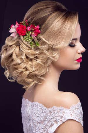 cabello rubio: Retrato de una hermosa chica rubia en la imagen de la novia con flores de color p�rpura en la cabeza. Cara de la belleza. Foto tirada en el estudio sobre un fondo gris