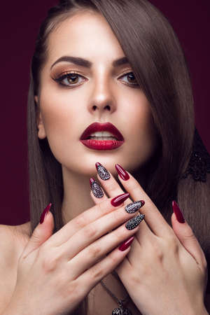 Pretty girl with unusual hairstyle, bright makeup, red lips and manicure design. Beauty face. Art nails. Studio portrait Archivio Fotografico