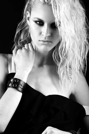 Daring girl model in black leather dress in the style of rock, dark make-up, wet hair and bracelets on her arms. Picture taken in the studio. Black-and-white image.