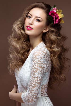 夜メイク、ウェディング ドレスで美しいブロンド女性が柔らかく唇とカール。花嫁のイメージ。美容顔。灰色の背景のスタジオでの撮影