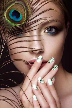 明るい化粧品で美しい少女は、彼女の顔にマニキュア デザインと孔雀の羽。爪のアート。写真はスタジオで撮影します。
