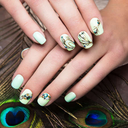 Art design manicure  with peacock feather on female hands. Close-up. Fashion nails. Photos shot in studio