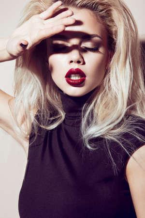 Hermosa chica rubia atractiva con los labios sensuales, la moda del cabello, vestido de negro. Cara de la belleza. Imagen tomada en el estudio