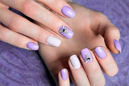 女性の手にクリスタルと美しい紫のマニキュア。クローズ アップ。スタジオでの撮影 写真素材