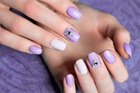short order: Beautiful purple manicure with  crystals on female hand. Close-up. Picture taken in the studio