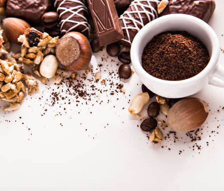 ground nuts: Roasted coffee beans, chocolate, candy, nuts and a cup with ground coffee and the place for the inscriptions on the white background.