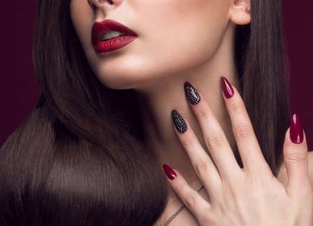 Pretty girl with unusual hairstyle, bright makeup, red lips and manicure design. Beauty face. Art nails. Studio portrait Standard-Bild