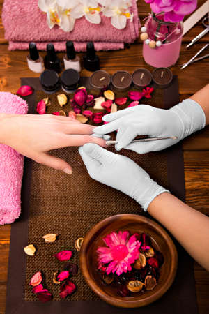 nailart: Closeup finger nail care by manicure specialist in beauty salon. Manicurist clear cuticle professional tool for manicure and pedicure.