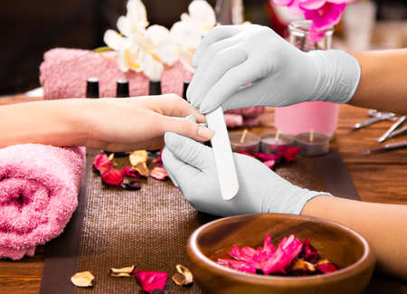Closeup finger nail care by manicure specialist in beauty salon. Manicurist clear cuticle professional nail file for manicure and pedicure.