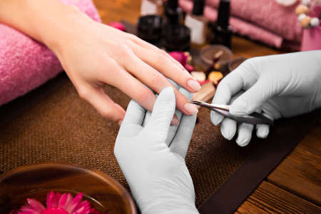 cuticle: Closeup finger nail care by manicure specialist in beauty salon. Manicurist clear cuticle professional nippers for manicure and pedicure. Stock Photo