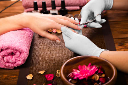 nailart: Closeup finger nail care by manicure specialist in beauty salon. Manicurist clear cuticle professional scissors for manicure and pedicure.