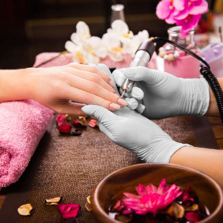 nailart: Closeup finger nail care by manicure specialist in beauty salon. Manicurist clear cuticle professional electric tool for manicure and pedicure.