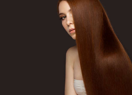 pretty hair: Beautiful Redheadgirl with a perfectly smooth hair and classic make-up. Beauty face. Picture taken in the studio on a white background.