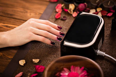 cuticle: Closeup finger nail care by manicure specialist in beauty salon. Manicurist clear cuticle professional electric Dryer for manicure and pedicure. Stock Photo