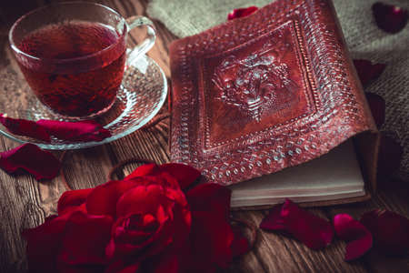 composition book: Composition consist of roses, hibiscus tea cup and note book on a wooden surface. Stock Photo