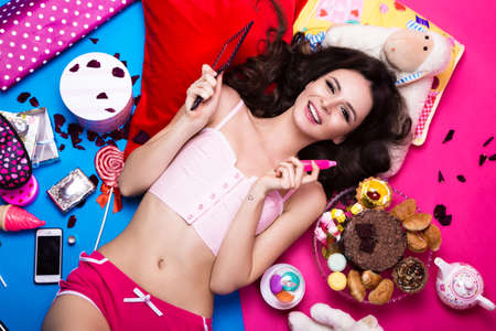 cute girl smiling: Beautiful fresh girl doll lying on bright backgrounds surrounded by sweets, cosmetics and gifts. Fashion beauty style. Photos shot in the studio.