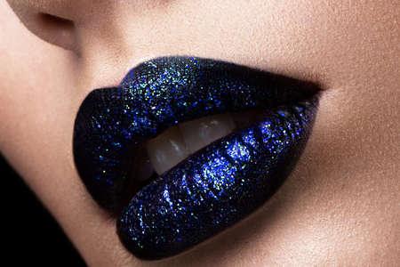 Brillante labios brillantes de cerca. brillo labial púrpura en negro. Foto de archivo