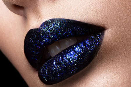 Brilliant glossy lips closeup. Purple glitter on black lipstick. Stock Photo