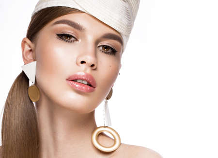 Pretty fresh girl in the image of modern Twiggy in fashionable white hat, with unusual eyelashes and accessories. Photos shot in studio