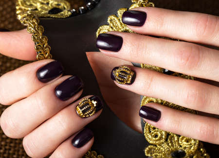 Black female manicure nails closeup with crown.