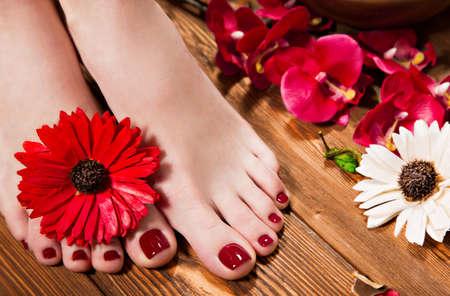 女性の手の美しい古典的な赤いペディキュア。クローズ アップ。花の背景のスタジオでの撮影