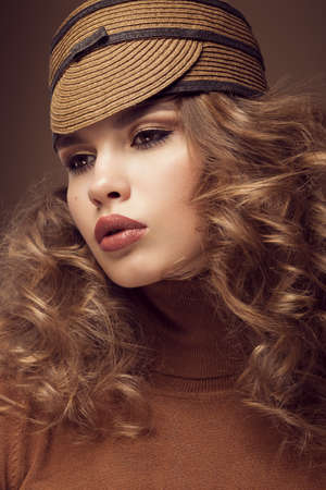 twiggy: Pretty fresh girl, image of modern Twiggy in fashionable brown hat, with unusual eyelashes and curls. Photos shot in studio Stock Photo