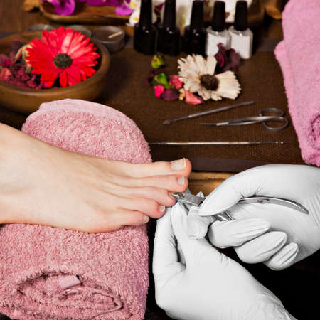 nailart: Closeup finger nail care by pedicure specialist in beauty salon. Pedicurist clear cuticle professional scissors for manicure and pedicure.