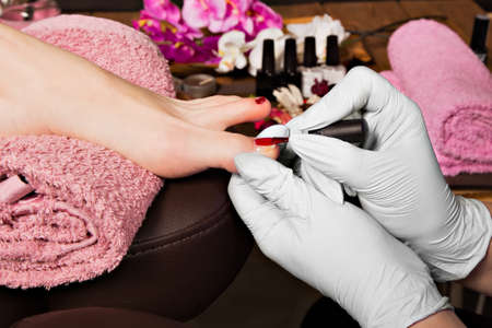 Closeup finger nail care by pedicure specialist in beauty salon. Pedicurist clear cuticle professional scissors for manicure and pedicure.