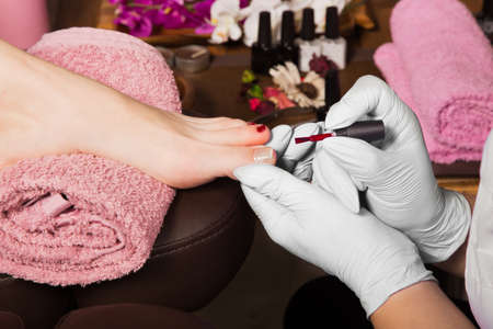 cuticle: Closeup finger nail care by pedicure specialist in beauty salon. Pedicurist clear cuticle professional scissors for manicure and pedicure.