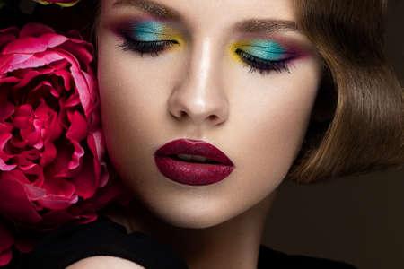 Bella ragazza colorato con il make-up, i fiori, la retro acconciatura La bellezza del viso. Foto scattate in studio