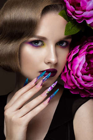 acrylic nails: Beautiful girl with colorful make-up, flowers, retro hairstyle and long nails. Manicure design. The beauty of the face. Photos shot in studio Stock Photo