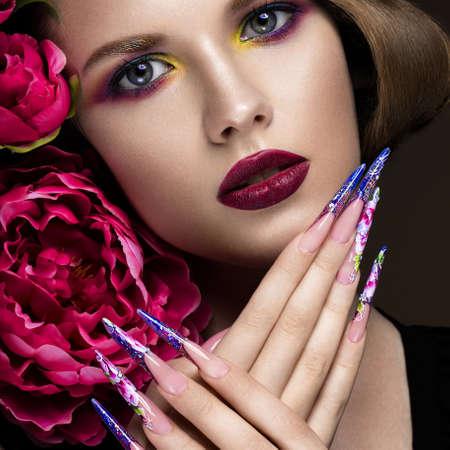カラフルな化粧、花、レトロな髪型と長い爪の美しい少女。マニキュアのデザイン。顔の美しさ。スタジオで撮影した写真