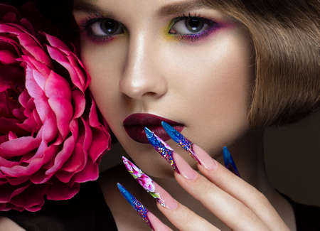 Beautiful girl with colorful make-up, flowers, retro hairstyle and long nails. Manicure design. The beauty of the face. Photos shot in studio Stok Fotoğraf - 57853907