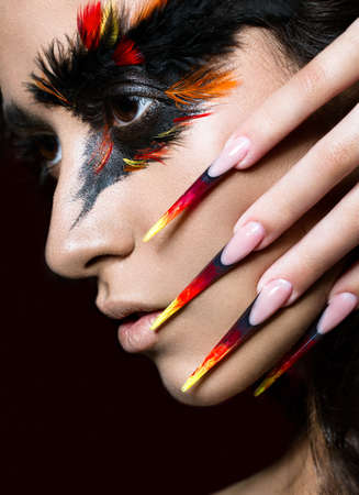 acrylic nails: Beautiful girl in the image of the Phoenix bird with creative makeup and long nails. Manicure design. The beauty of the face. Photos shot in studio Stock Photo