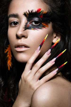 Beautiful girl in the image of the Phoenix bird with creative makeup and long nails. Manicure design. The beauty of the face. Photos shot in studio Stock Photo