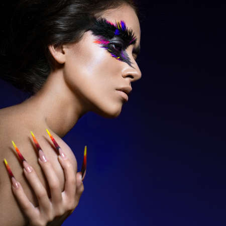 nails woman: Beautiful girl in the image of the Phoenix bird with creative makeup and long nails. Manicure design. The beauty of the face. Photos shot in studio Stock Photo