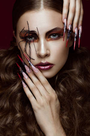 Portrait of woman in the image of spider with creative art makeup and long nails. Manicure design, beauty face. Photos shot in studio Imagens