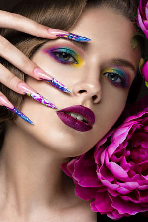 Beautiful girl with colorful make-up, flowers, retro hairstyle and long nails. Manicure design. The beauty of the face. Photos shot in studio Banque d'images