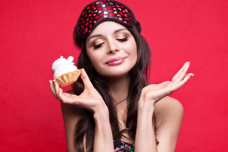 Funny young woman in sleeping mask and pajamas, sweets in the hands on a red background. The beauty of the face. Photos shot in studio Stock Photo