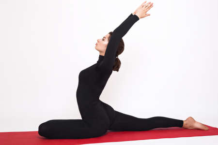 yogic: Beautiful athletic girl in a black suit doing yoga. Eka Pada Radzhakapotasana asana - pigeon pose royal. Isolated on white background.