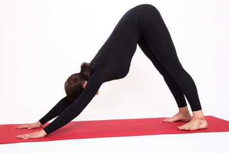 Mooi atletisch meisje in een zwart kostuum die yoga doen. Adho Mukha Svanasana asanas - honden poseren voor de mond. Geïsoleerd op witte achtergrond Stockfoto