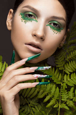 アート メイクで美しい少女は、シダの葉し、長い爪します。マニキュアのデザイン。顔の美しさ。スタジオで撮影した写真