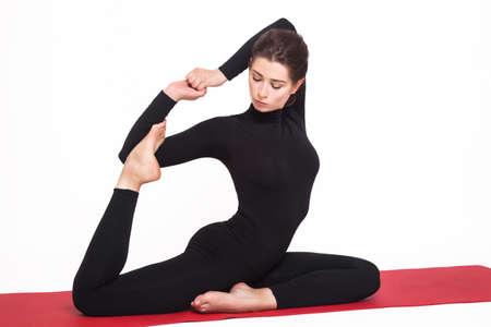 eka: Beautiful athletic girl in a black suit doing yoga. eka pada rajakapotasana asana - pigeon pose royal. Isolated on white background. Stock Photo