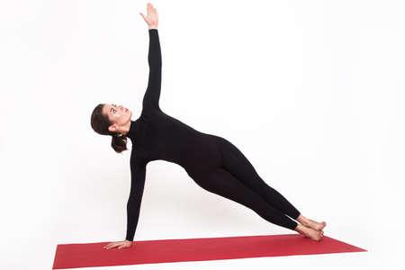 yogic: Beautiful athletic girl in black suit doing yoga. vasishthasana asana sage pose. Isolated on white background.