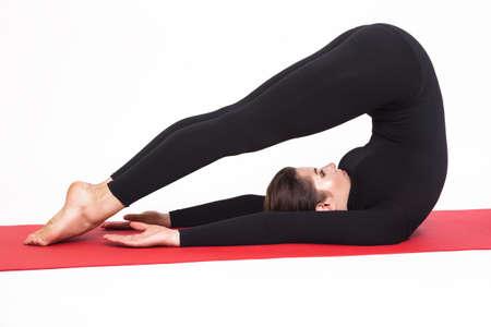 yogic: Beautiful athletic girl in a black suit doing yoga. halasana asana - plow pose . Isolated on white background.