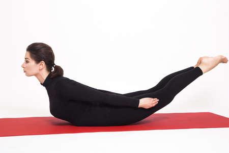 ashtanga: Beautiful athletic girl in black suit doing yoga. viparita naukasana asana boat pose. Isolated on white background. Stock Photo