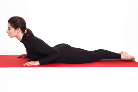bhujangasana: Beautiful athletic girl in a black suit doing yoga. bhujangasana asana - cobra pose . Isolated on white background.