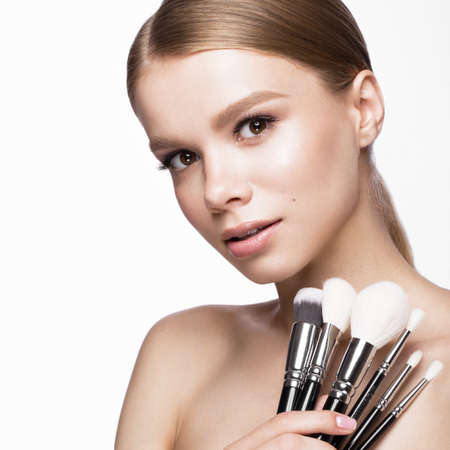 Beautiful young girl with a light natural make-up,brushes for cosmetics and French manicure. Beauty face. Picture taken in the studio on a white background. Stock Photo